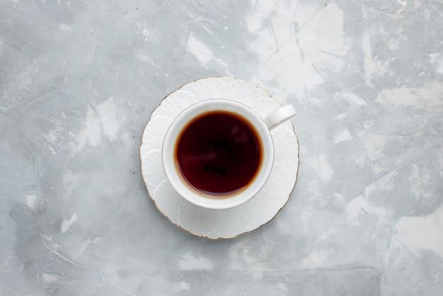 Vista superior de uma xícara de chá quente dentro de uma xícara branca acesa, bebida de chá doce