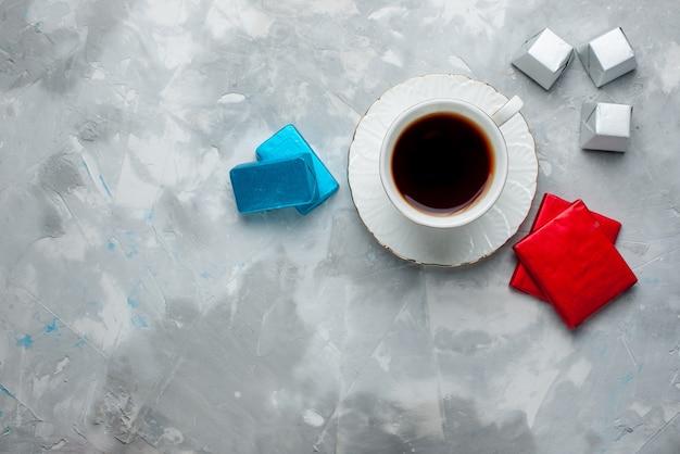 Vista superior de uma xícara de chá quente dentro de uma xícara branca com um pacote de bombons de chocolate prateado na mesa leve, uma bebida de chá doce na hora do chá