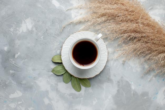 Vista superior de uma xícara de chá quente dentro de uma xícara branca na luz, cerimônia de café da manhã com bebida de chá