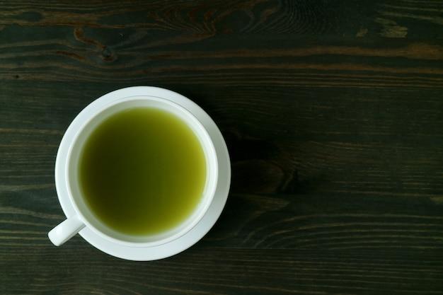 Vista superior de uma xícara de chá verde matcha quente isolada em uma mesa de madeira