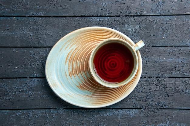 Vista superior de uma xícara de chá xícara branca e pires em fundo escuro