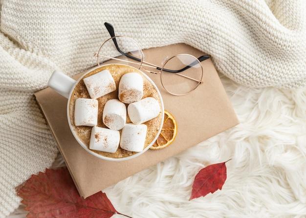 Vista superior de uma xícara de chocolate quente com marshmallows no livro com óculos
