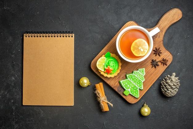 Vista superior de uma xícara de cone de conífera de acessórios de ano novo de chá preto e limão com canela ao lado do caderno em fundo preto