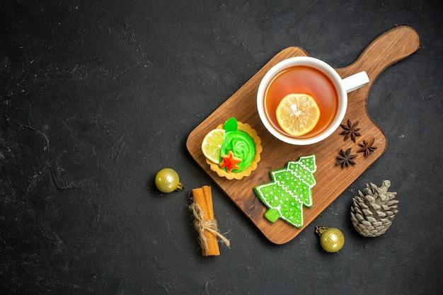 Vista superior de uma xícara de cone de conífera de acessórios de ano novo de chá preto e limão com canela em fundo preto