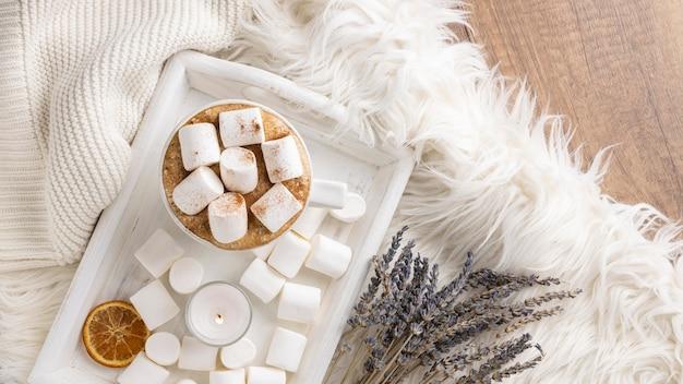 Vista superior de uma xícara de marshmallows na bandeja com lavanda e frutas cítricas secas