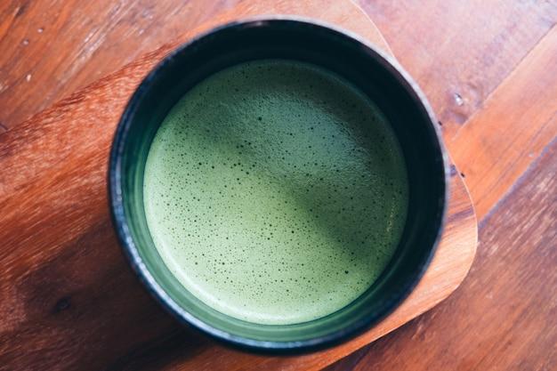 Vista superior de uma xícara de matcha quente com leite no chão de madeira