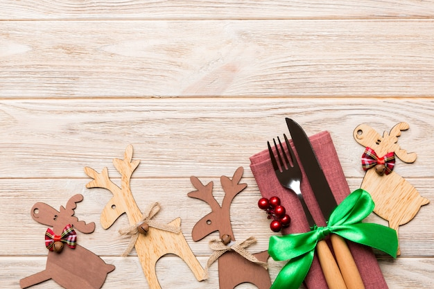 Vista superior de utensílios de ano novo em guardanapo com decorações do feriado e renas em fundo de madeira. conceito de jantar de natal com espaço de cópia