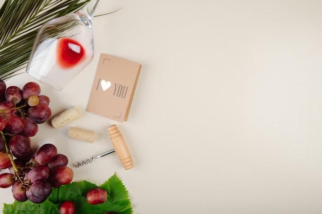 Vista superior de uva fresca, pequeno cartão postal, parafuso de garrafa e um copo de vinho deitado na mesa branca com espaço de cópia
