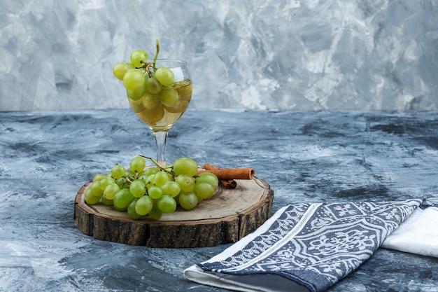 Vista superior de uvas brancas, canela, copo de uísque na placa de madeira com toalha de cozinha em fundo de mármore azul claro e escuro. horizontal