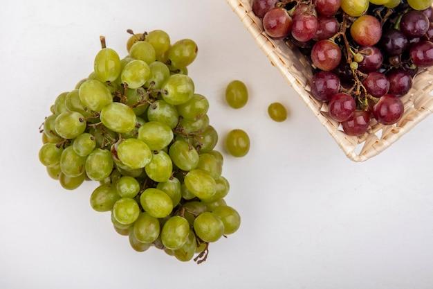 Vista superior de uvas brancas e uvas vermelhas em uma cesta no fundo branco