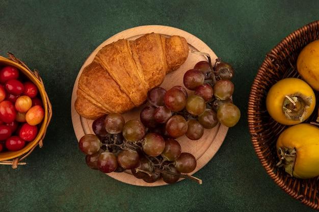 Vista superior de uvas doces em uma placa de cozinha de madeira com croissant com frutas de caqui em um balde em uma superfície verde
