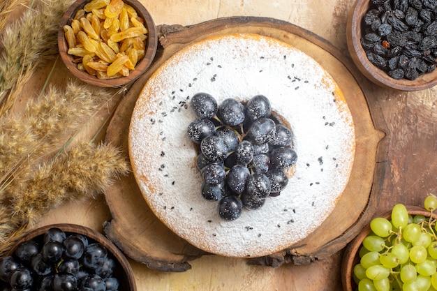 Vista superior de uvas em close-up, um bolo com taças de uvas passas e espiguetas de uvas