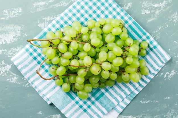 Vista superior de uvas em gesso e toalha de cozinha