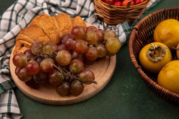 Vista superior de uvas em uma placa de cozinha de madeira em um pano xadrez com croissant com frutas de caqui em um balde sobre um fundo verde