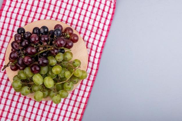 Vista superior de uvas em uma tábua de corte em tecido xadrez e em fundo cinza com espaço de cópia
