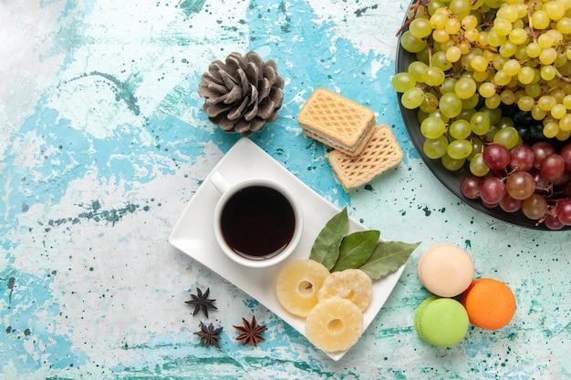 Vista superior de uvas frescas coloridas com uma xícara de chá, macarons e waffles em um fundo azul claro fruta baga fresco suco maduro vinho