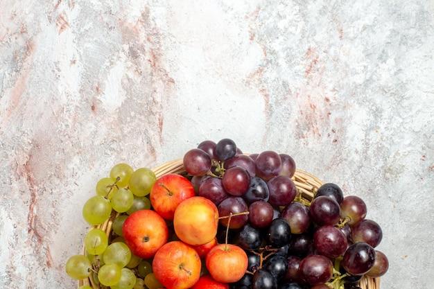 Vista superior de uvas frescas com ameixas em uma superfície branca clara