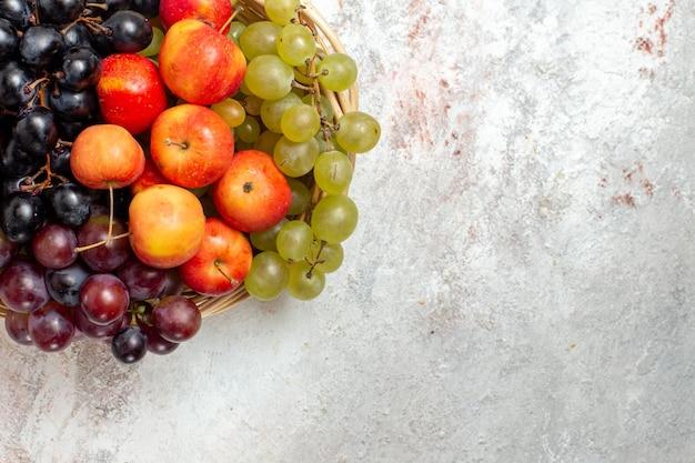 Vista superior de uvas frescas com ameixas na superfície branca