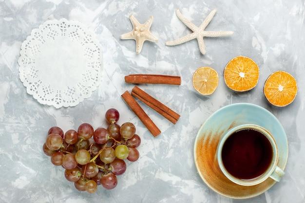 Vista superior de uvas frescas com canela e xícara de chá na mesa branca