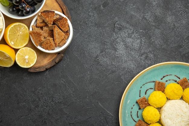 Vista superior de uvas frescas com doces de bolo e limão em comida de leite de fruta refeição de superfície escura