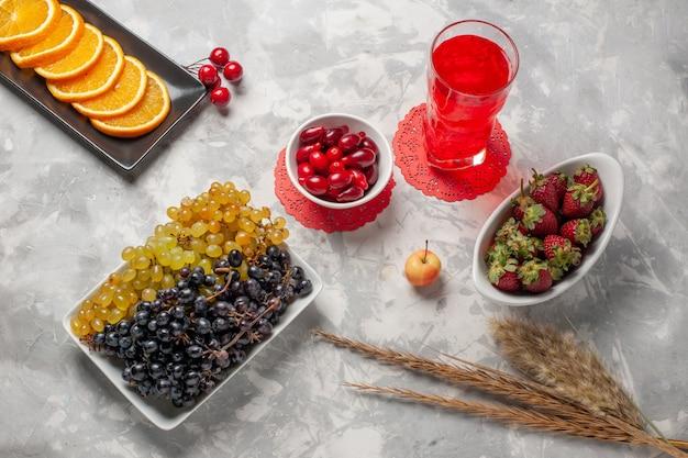 Vista superior de uvas frescas com dogwoods e morangos na superfície branca fruta baga tropical exótica fresca