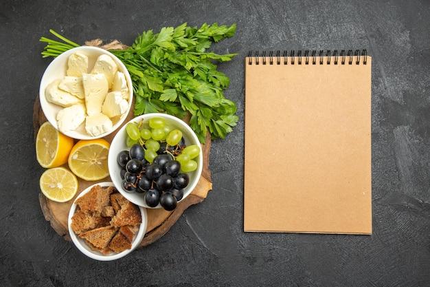 Vista superior de uvas frescas com folhas de queijo branco e fatias de limão na refeição escura de frutas com leite