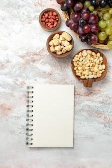Vista superior de uvas frescas com nozes e bloco de notas na superfície branca