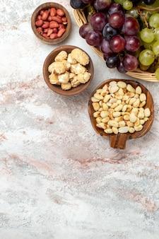 Vista superior de uvas frescas com nozes na superfície branca