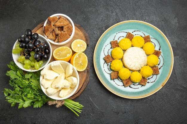 Vista superior de uvas frescas com queijo branco, doces e limão na superfície escura.
