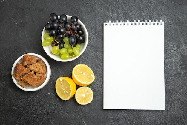 Vista superior de uvas frescas com rodelas de limão na superfície escura de frutas maduras