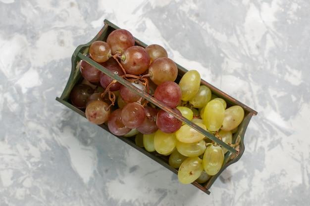 Vista superior de uvas frescas dentro de uma mesa de madeira na superfície branca.