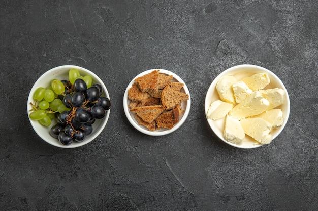 Vista superior de uvas frescas e maduras com pão e queijo na superfície escura refeição com leite e frutas