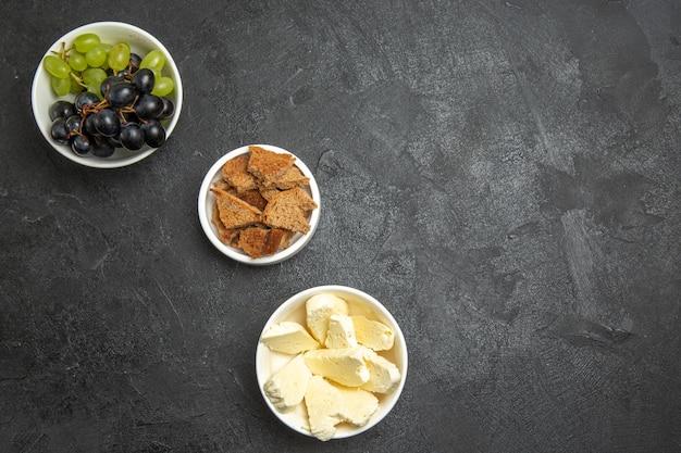 Vista superior de uvas frescas e maduras com queijo branco e pão fatiado em superfície escura refeição alimentar frutas lácteas
