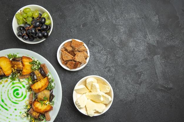 Vista superior de uvas frescas e maduras com queijo branco e rolinhos de berinjela em uma superfície escura com comida e frutas lácteas