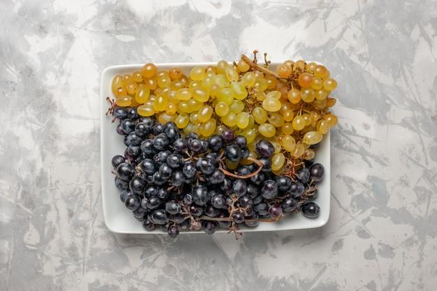 Vista superior de uvas frescas suculentas dentro do prato na superfície branca vinho frutas frescas maduras