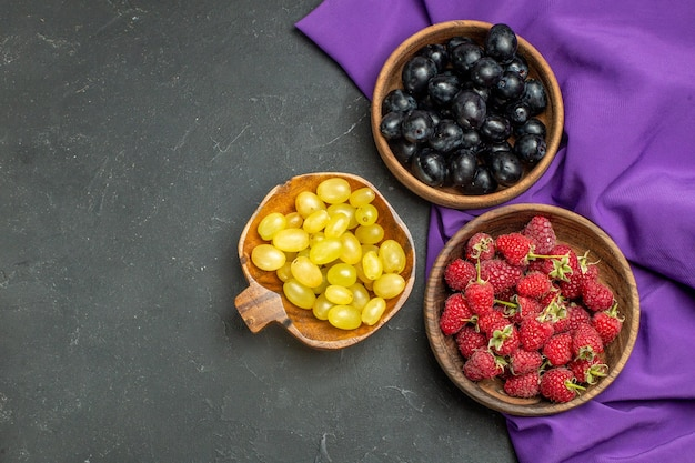 Vista superior de uvas pretas e amarelas de framboesas em taças xale roxo na superfície escura e isolada no espaço livre