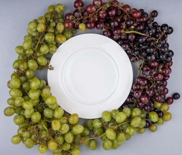 Vista superior de uvas pretas e brancas ao redor da placa em fundo cinza