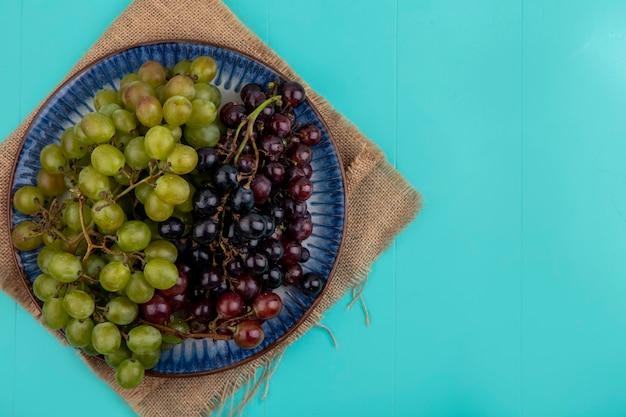 Vista superior de uvas pretas e brancas em prato e saco sobre fundo azul com espaço de cópia