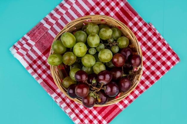 Vista superior de uvas pretas e brancas em uma cesta em pano xadrez sobre fundo azul