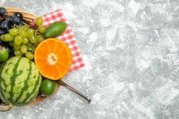Vista superior de uvas pretas frescas com laranja e feijoa em frutas brancas superficiais maduras frescas