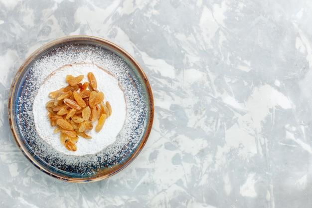 Vista superior de uvas secas de passas em pó dentro do prato na mesa branca