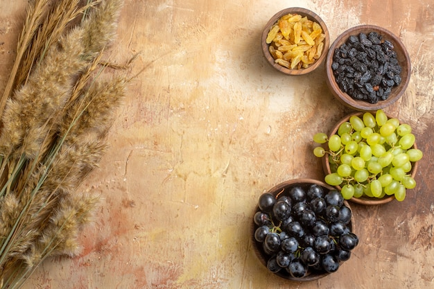 Vista superior de uvas, uvas, passas nas tigelas, espiguetas sobre a mesa