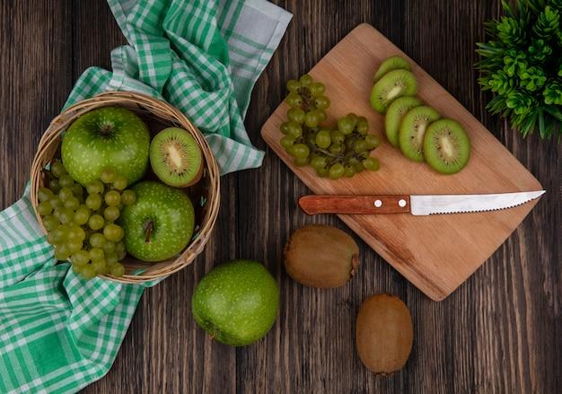 Vista superior de uvas verdes com fatias de kiwi e uma faca em uma placa e maçãs verdes em uma cesta em uma toalha verde quadriculada em um fundo de madeira
