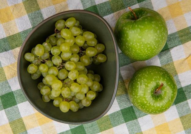 Vista superior de uvas verdes com maçãs verdes em uma toalha xadrez verde-amarela
