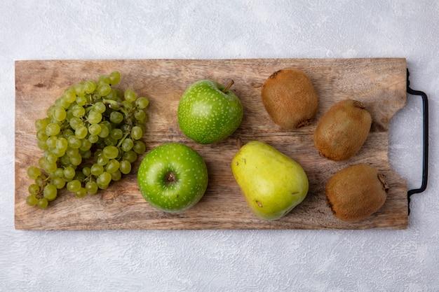 Vista superior de uvas verdes com maçãs verdes, pera e kiwi em um suporte contra um fundo branco