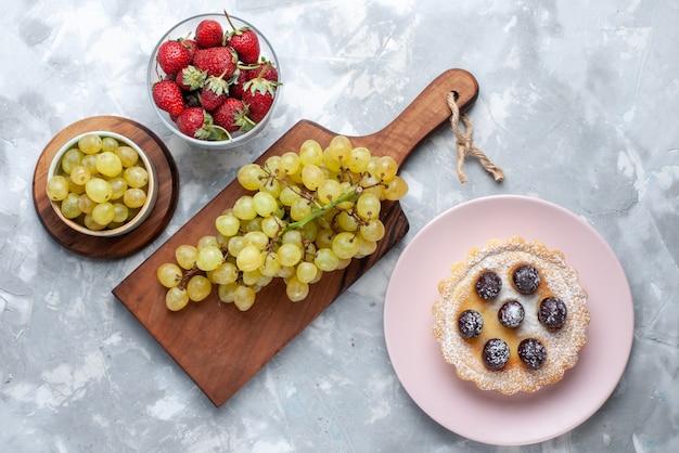 Vista superior de uvas verdes com morangos vermelhos na mesa de luz, bolo de frutas fresco de verão