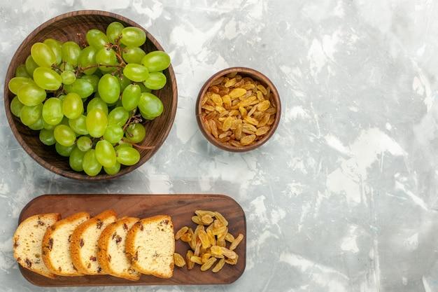 Vista superior de uvas verdes frescas com passas e fatias de bolo em uma mesa branca clara