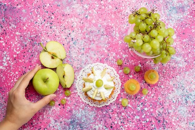 Vista superior de uvas verdes frescas, frutas totalmente azedas e deliciosas com um pequeno bolo na luz, suco fresco de frutas