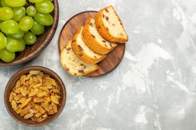 Vista superior de uvas verdes frescas suaves e deliciosas com bolos em uma mesa branca clara