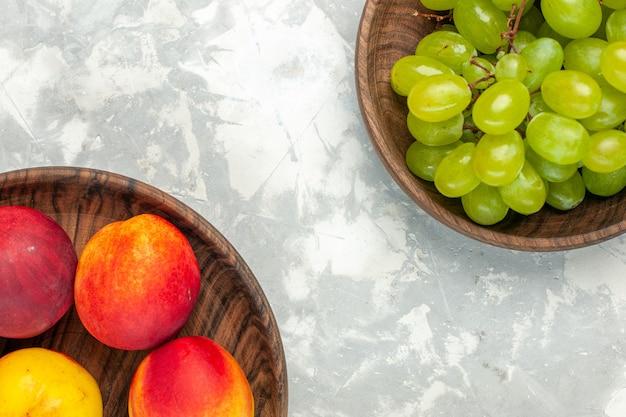 Vista superior de uvas verdes frescas suaves e deliciosas com pêssegos em uma mesa branca clara